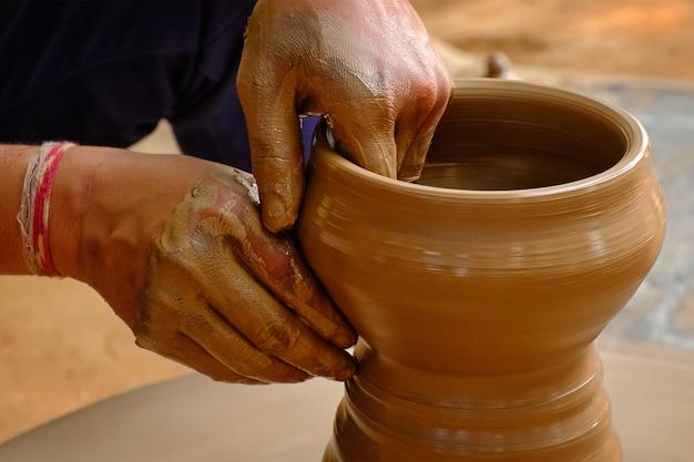 도기-도공 휠에 점토를 형성하는 도공의 숙련 된 젖은 손