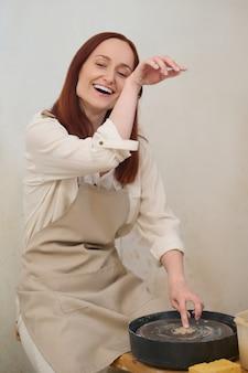 Гончарный круг. женщина-гончар работает на гончарном круге в мастерской