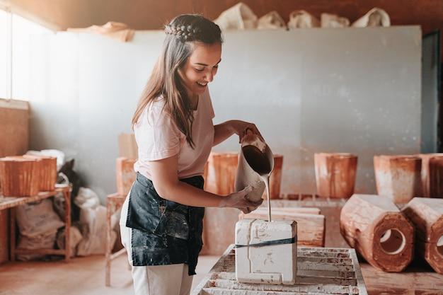 도자기 여자는 나중에 그림을 만들기 위해 금형에 시멘트를 넣는 작업장에서