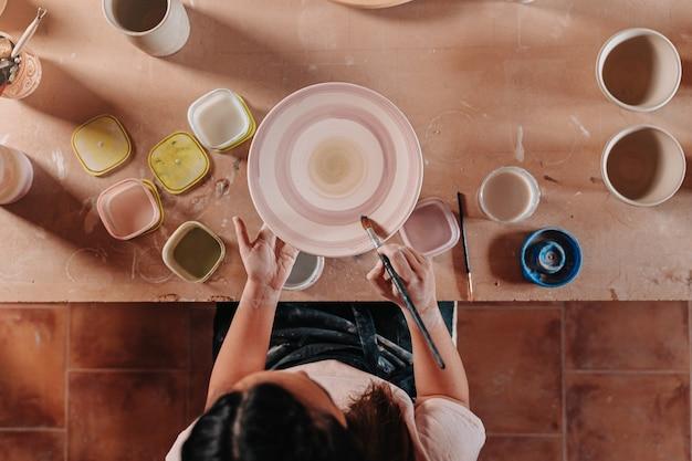 다른 도구와 여러 색상으로 그녀의 테이블에 그녀의 예술 작품을 그리는 그녀의 워크샵에서 도자기 여자