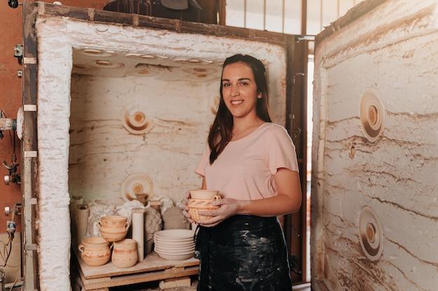 오래된 가마에서 손으로 만든 작품을 꺼내는 도자기 여자