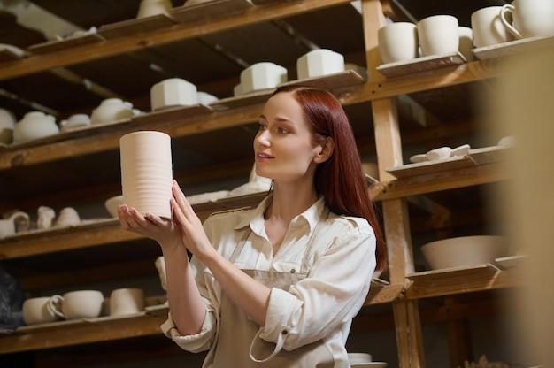 Гончарная мастерская. милая молодая женщина-гончар в своей мастерской
