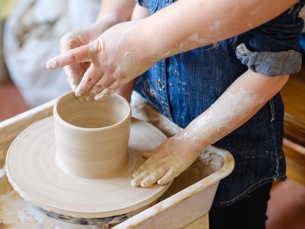 Гончарная мастерская. поделки ручной работы. ремесленник учит девочку лепить из глины на гончарном круге