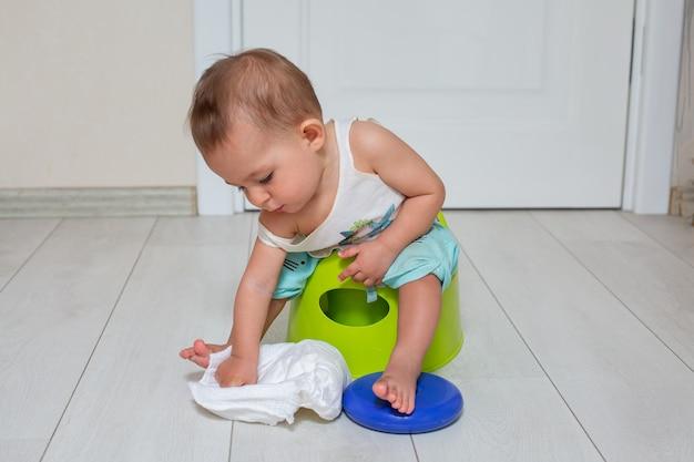 Концепция приучения к горшку милый маленький ребенок сидит на зеленом горшке и играет с подгузником в комнате