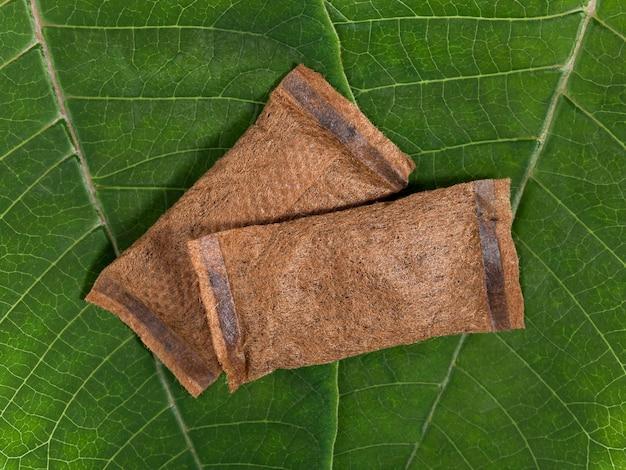 Мешочки бездымного табака на зеленых листьях. вид сверху. макросъемка