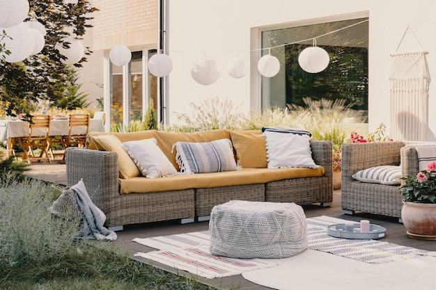 Пуф рядом с диваном и креслом из ротанга на деревянной террасе с цветами и лампами