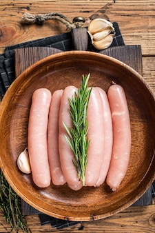 Poultry raw sausages in a wooden palte with herbs