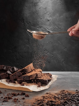 Pound chocolate cake standing on a gray table sprinkled with cocoa from a sieve.