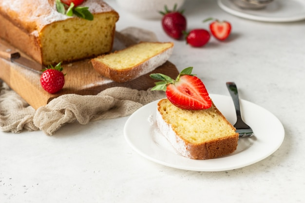 Pound or loaf cake with strawberry and mint on wooden board.