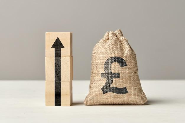 Концепция роста валюты фунта стерлингов с мешком стрелки и денег вверх.