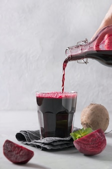 Pour beetroot juice from bottle in glass. close up. vertical orientation.