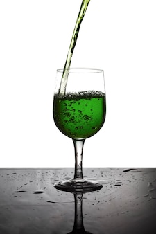 Pour the green water  into a glass of wine.