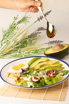 Pour honey from spoon to salad consists of sliced avocado, boiled egg, lettuce, lettuce, tomato and biscuits, topped with salad cream, avocado cut in half on the back, a meal with a lot of vegetables.