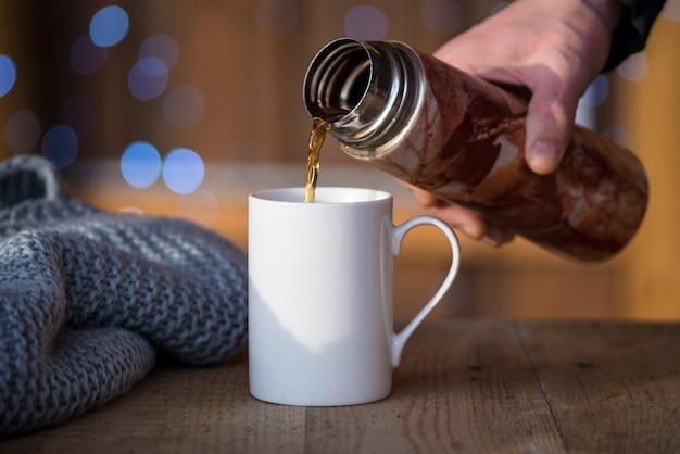 白い磁器のマグカップにホットコーヒーを注ぐ