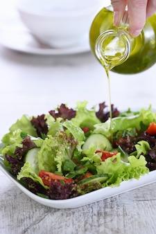 野菜サラダにレモンを注ぐ-バターボートからのオリーブドレッシング