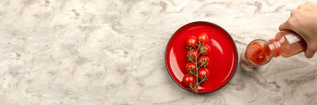トマトジュースをグラスに注ぎます。手はボトルからガラス、大理石のテーブルトップの背景にトマトジュースを注ぎます。バナーコピースペース
