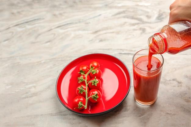 ガラスの手にトマトジュースを注ぐボトルからガラスの大理石のテーブルトップにトマトジュースを注ぐ