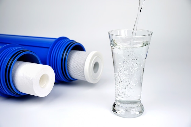 Pour water into a glass with water filters separate on white background