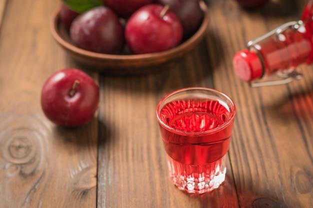 木製のテーブルにプラムリキュール、ボトル、熟したベリーをグラスに注ぎました。ベリープラムから作られた自家製のアルコール飲料。上からの眺め。