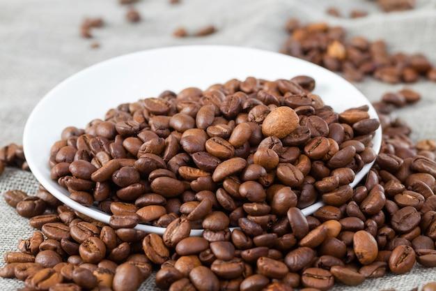 Залитые на белую круглую тарелку обжаренные зерна темного вкусного кофе на скатерти, крупный план кухонной утвари на льняной скатерти