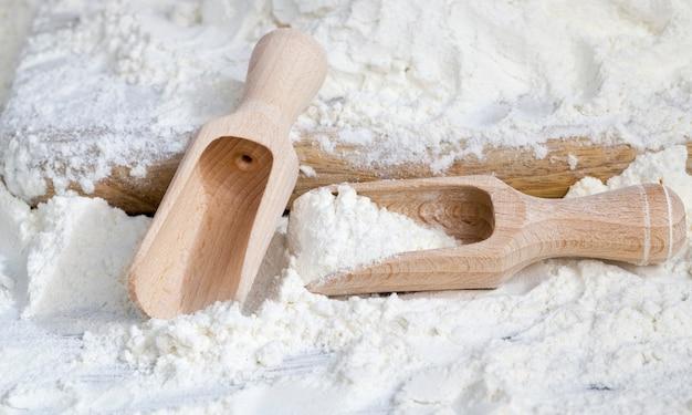 古い木の板に白小麦粉を注ぎ、調理中のクローズアップ、木のスプーンの隣