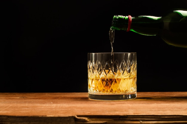 木製のテーブルと暗闇にウイスキーのグラスを注ぐ