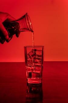 アイスキューブの完全なガラスにアルコールを注ぐ