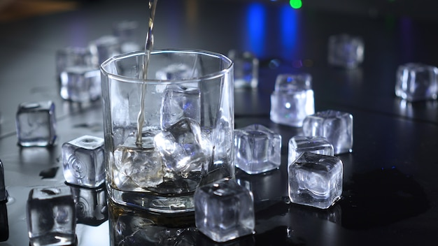 Pouring alcoholic beverages in glass with ice cubes.