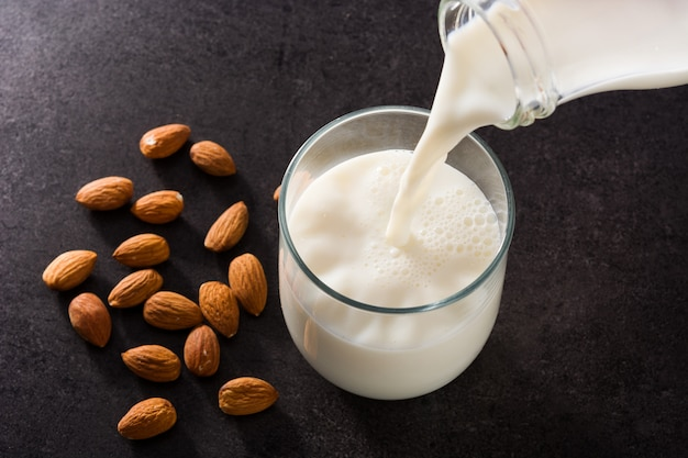 Pouring almond milk in glass on black