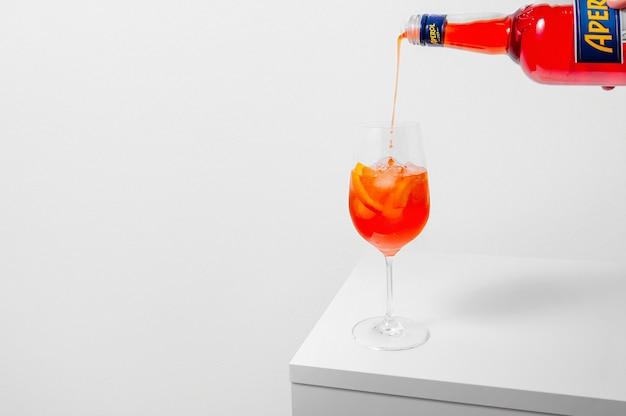 흰색 바탕에 얼음으로 와인 잔에 aperol을 붓는