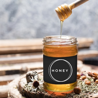 Pouring aromatic honey into jar, sweet honey dripping from dipper into jar