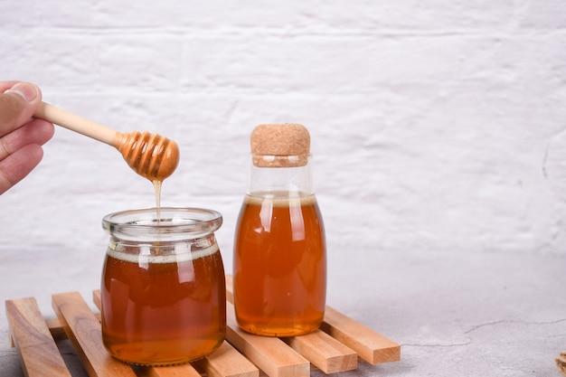 芳香族の蜂蜜を瓶の空白に注ぐ