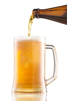 Pouring beer from bottle into a mug with foam isolated