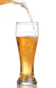 白で隔離されるボトルからビールを注ぐ