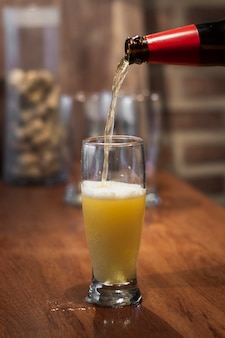 Pouring beer from bottle to pint process