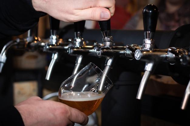 パブで銀色のバーの蛇口からビールを注ぐ