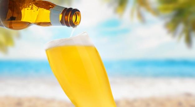 바다 해변에서 유리에 맥주를 붓는