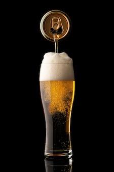 黒の背景に分離されたガラスにビールを注ぐ