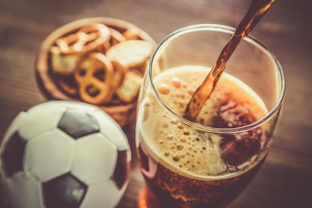 Разлив пива в бокал с закусками и футболом