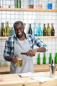 쏟아지는 맥주. 바 카운터에 서서 병에서 맥주 머그잔에 맛있는 맥주를 붓는 동안 행복감을 느끼는 즐거운 긍정적 인 전문 바텐더