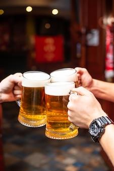 Разливное пиво стоя у барной стойки. большое крафтовое пиво в разливе в меню кафе или паба. поджаривание с друзьями в баре