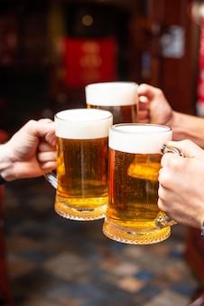Разливное пиво стоит у барной стойки, поджаривая большое крафтовое пиво в пабе