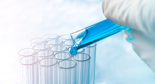 Pouring blue liquid into a test tube. scientific experiment. development of technology and medicine.