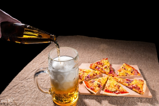 Pouring bottled beer into glass mug with meal of fresh baked pizza arranged in slices on wooden cutting board on burlap covered table