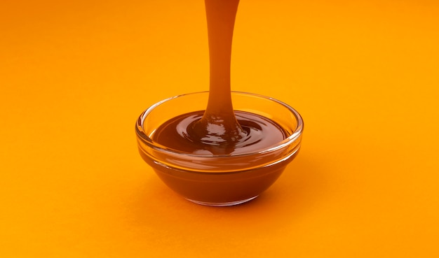 Pouring caramel sauce on orange surface