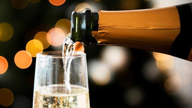 新年の前にシャンパンをガラスに注ぐ