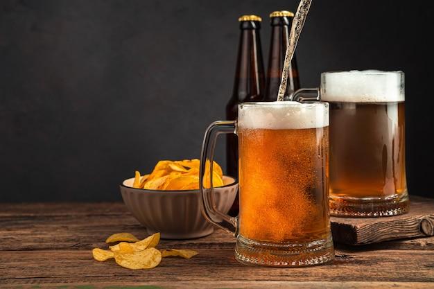 어두운 갈색 배경에 있는 맥주 머그에 차가운 맥주를 붓는 것 복사를 위한 측면 보기 공간