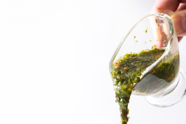 Pouring chimichurri sauce on white surface copyspace.