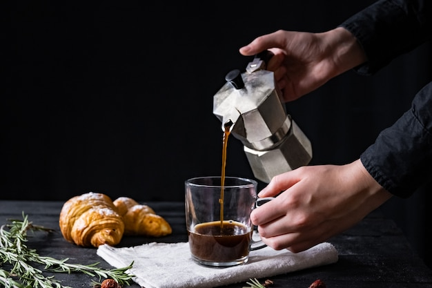 Заливка кофе из итальянского перколятора, снятого в сдержанном виде мужские руки наливают черный кофе от итальянского пивовара мока