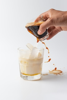 Pouring coffee into cup ice milk on white background.
